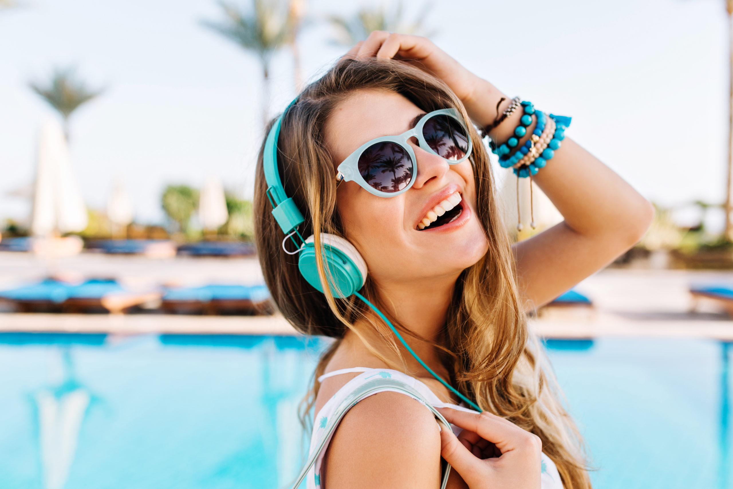 close up portrait joyful laughing young lady trendy bracelets posing with hand up near open air blue swimming pool scaled